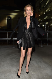 Eva Herzigova looked fiercely sexy in a plunging black leather dress by Saint Laurent while attending the brand's fashion show.