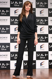 Angelina Jolie donned a sleek black wrap top with her slacks for the 'Salt' press conference in Japan.