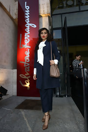 Sonam Kapoor attended the Salvatore Feragamo fashion show wearing a navy pantsuit with a white tie-neck blouse.