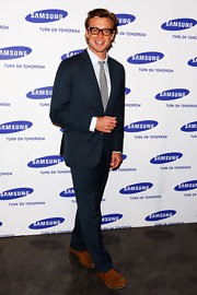 Simon Baker looks sharp at a Samsung event in a slim-fit steely blue suit. Thick-rimmed eye wear, a pale gray tie and cognac shoes complete the actor's smart look.