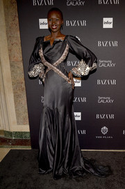 Alek Wek was medieval-chic at the Harper's Bazaar Icons event in a black gown with blouson sleeves, a square neckline, and crisscross detailing.