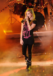 Avril wears skinny patent leather pants with her 'What the Hell' t-shirt on stage.