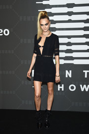 Cara Delevingne added a tough-chic touch with a pair of black lace-up boots.
