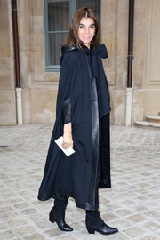Carine Roitfeld went for a dramatic winter look in a leather-trimmed black cape during the Schiaparelli fashion show.