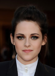 Kristen countered her boyish jacket with a feminine updo featuring a hidden braid and loose tendrils.