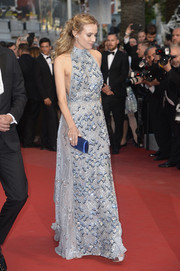 Diane Kruger accessorized with an elegant satin clutch that echoed the blue accents of her dress.