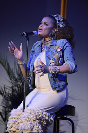 Andra Day performed at the Haiti Takes Root benefit wearing a bauble-embellished denim jacket over a ruffle-hem dress.