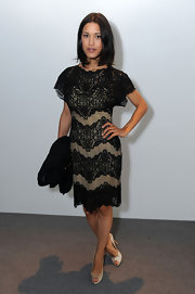 Julia Jones was elegant in a black and nude tulle cocktail dress with embroidered lace drop sleeves. She finished off the look with peep-toe pumps.