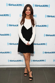 Selena Gomez visited 'The Morning Mash Up' wearing a Victor Glemaud ensemble, consisting of a black slip dress layered over a white sweater.