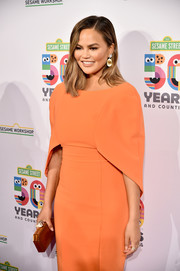 Chrissy Teigen paired a geometric gold clutch with a caped coral dress for the Sesame Workshop 50th anniversary benefit gala.