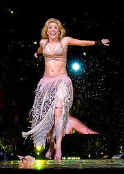 Shakira is a burst of energy on stage in a nude wrap-around swim top and flowing skirt.