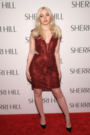 Dove Cameron looked totally ready for Valentine's Day in this beaded red cutout dress by Sherri Hill while attending the label's fashion show.