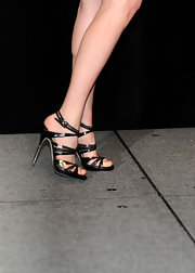 "The ""Dear John"" star wore a hot pair of black strappy sandals with her asymmetrical ensemble. The bold footwear added an edgy look to her light-colored cocktail dress."