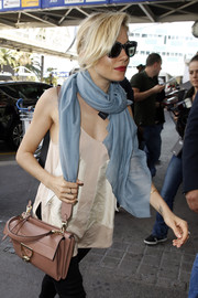 Sienna Miller styled a simple cami with a pastel-blue silk scarf for a day out at Nice.