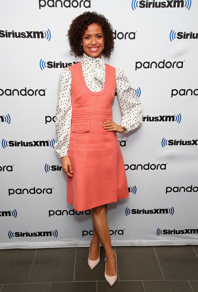 Gugu Mbatha-Raw visited SiriusXM's Town Hall wearing a coral pinafore dress over a dotted white blouse.