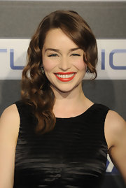 Emilia Clarke completed her glamorous looks with a pretty shade of gold-infused red lipstick.
