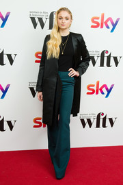 Sophie Turner polished off her look with a black satin trenchcoat.