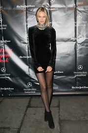 Candice Swanepoel toughened her velvet mini dress with a bold statement necklace and black suede ankle boots.