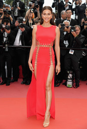 Irina Shayk sealed off her head-turning look with gold Versace sandals.
