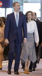 Queen Letizia of Spain attended FITUR wearing a gray handkerchief-hem plaid skirt by Massimo Dutti paired with a white blouse.