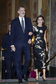 Queen Letizia paired her lovely dress with black and gold cross-strap sandals by Magrit.