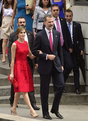 Queen Letizia of Spain complemented her lovely dress with a red satin-panel clutch by Magrit.