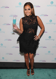 Adrienne Bailon looked saucy in a black lace peplum dress during the Sparkle Louder launch.