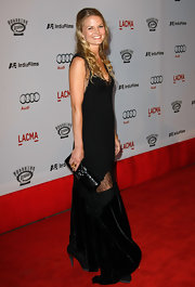 Jennifer is carrying a patent leather roll clutch, in black.