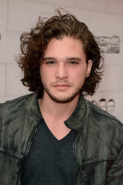 Kit Harington styled his messy curls in a swept back 'do.