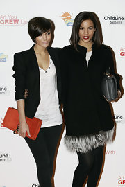 Frankie Sandford layered a strong-shouldered black blazer over a white burnout tee.