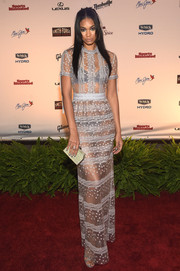 Chanel Iman added shimmer to her look with a metallic gold clutch.