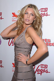Abbey Clancy strikes a sexy pose while wearing a silver dial watch.