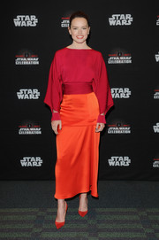 Daisy Ridley rounded out her striking ensemble with a pair of red-orange Louboutin pumps.