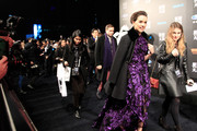 Daisy Ridley arrived for the 'Star Wars' Shanghai fan event wearing a black military coat over a purple floral gown.