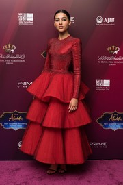 Naomi Scott looked absolutely breathtaking in a red Armani Privé gown with a fitted top and a tiered skirt at the VIP screening of 'Aladdin' with the Jordanian Royal Family.
