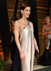 Hilary Rhoda paired a diamond cuff with a metallic one-shoulder gown for a stunning look during the Vanity Fair Oscar party.