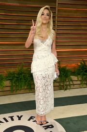 Rita Ora went to the Vanity Fair Oscar party looking ultra girly in a white lace peplum dress by Miu Miu.
