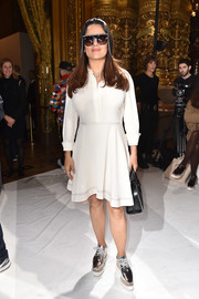Salma Hayek kept it casual in a white shirtdress while attending the Stella McCartney fashion show.