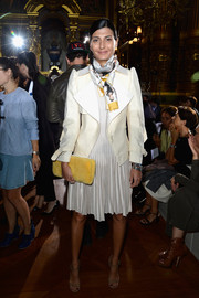 Giovanna Battaglia layered a white jacket with oversized lapels over a pleated dress for a sharp and chic look during the Stella McCartney fashion show.