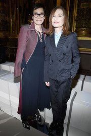 Isabelle Huppert worked her trademark masculine-chic style with this gray pinstriped suit by Stella McCartney during the brand's Fall 2018 show.