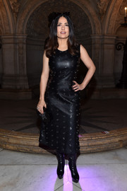 Salma Hayek cut a bold figure in a grommeted black leather dress by Stella McCartney during the brand's fashion show.