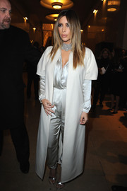 Kim Kardashian looked like a modern princess at the Stephane Rolland fashion show in an ankle-length white coat layered over a silver jumpsuit.