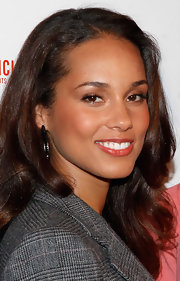 Creating a natural flush like Alicia Keys' takes only a few seconds, especially when you let your lipstick do double duty. Find a satin formula in a  shade similar to your own natural lip color with a slight tinge of pink or red. A great product option to try is Clinique High Impact Lip Color. Sweep a little on your lips, dab a bit on the apples of your cheeks and blend.