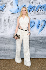 Ellie Bamber punctuated her look with a nude and black houndstooth clutch.