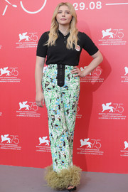 Chloe Grace Moretz jazzed up her simple top with a pair of feather-hem print pants, also by Miu Miu.