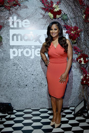 Laila Ali cut a curvy silhouette in this form-fitting coral dress at the T.J. Maxx event.