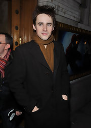Reeve looks sophisticated in a rustic brown scarf and wool coat jacket.