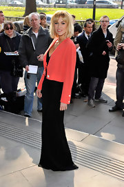 Katherine goes bold in a salmon blazer over a dramatic floor length black evening dress.