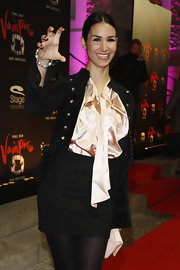 Sila Sahin toughened up her silk blouse and miniskirt ensemble with a brass-buttoned military jacket.