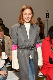 Olivia Palermo attended the Taoray Wang fashion show wearing a gray coat, which she cinched in with a studded black belt.